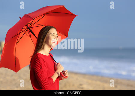 Portrait of a happy girl with red umbrella on the beach at sunset with the horizon and sea in the background - Stock Photo