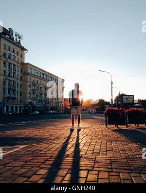 man looking at sunset in the city, Minsk, Belarus - Stock Photo