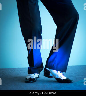 Male latin and salsa dancer in black and white jazz dancing shoes in light and dark on stage. - Stock Photo