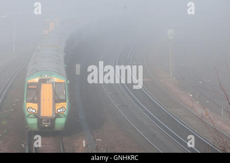 Trains struggling through a foggy morning - Stock Photo