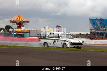 A 1965 Mk1, Ford lotus Cortina  with wing damage and a smoking front tyre, during the qualifying session for the - Stock Photo