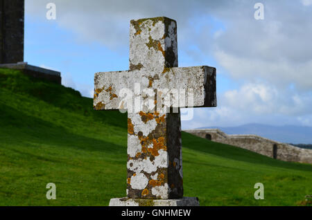 Old stone cross in Ireland with lichen growing on it in Ireland. - Stock Photo