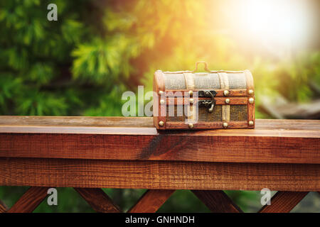 Closed wooden chest box outdoors in nature. Selective focus, lens flare. - Stock Photo