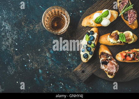 Italian crostini with various toppings on round wooden board and glass of rose wine over black plywood background, - Stock Photo