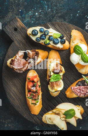 Italian crostini with various toppings on round wooden serving board over black plywood background, top view - Stock Photo