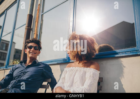Shot of young man and woman sitting outdoors and talking. Young couple spending time together. - Stock Photo