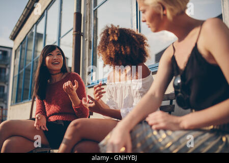 Multiethnic group of female friends sitting outdoors and talking. Young women sitting in balcony. - Stock Photo