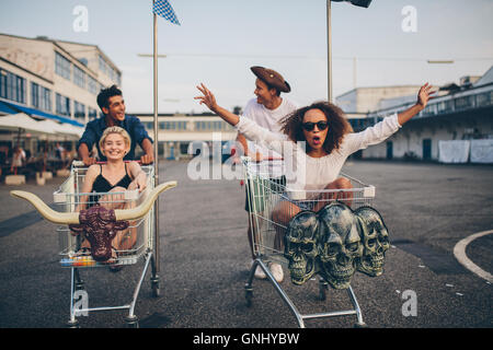 Young friends having fun on a shopping trolley. Multiethnic young people racing on shopping cart. - Stock Photo