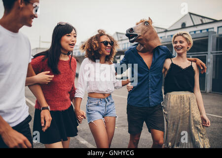 Shot of diverse group of friends having fun together outdoors. Young men and women walking outdoors, with one man - Stock Photo