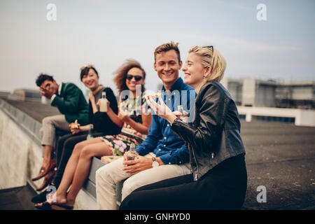 Shot of young people partying on terrace. Multiracial friends sitting together on rooftop having drinks and eating. - Stock Photo