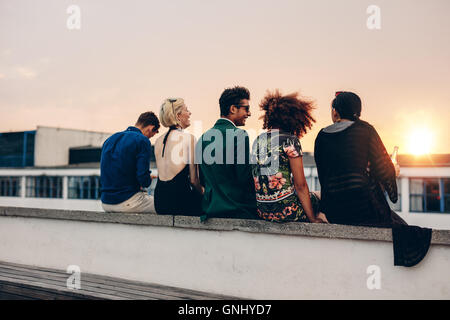 Rear view shot of young men and women sitting together on rooftop. Mixed race friends relaxing on terrace during - Stock Photo