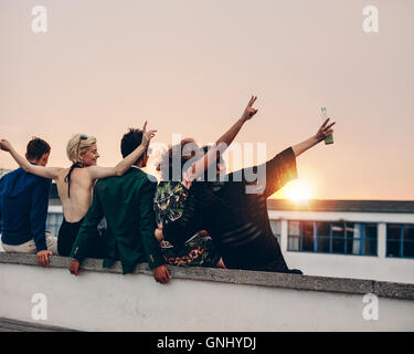Rear view of young people partying on terrace with drinks at sunset. Young men and women enjoying drinks on rooftop - Stock Photo