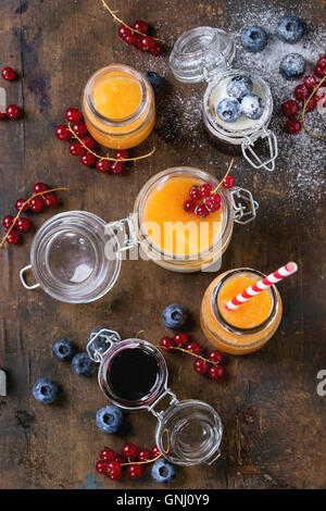 Variety of melon and blueberries smoothie in glass jars and bottle with yogurt and red currant berry, served over - Stock Photo