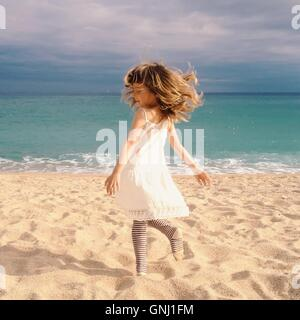 Girl spinning around on beach - Stock Photo