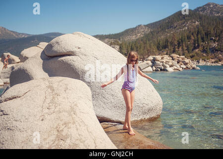 Girl standing on rocks with brother in background Lake Tahoe, California, America, USA - Stock Photo