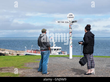 Tourists looking at the famous multi-directional signpost at John O'Groats, Caithness, Scotland - Stock Photo