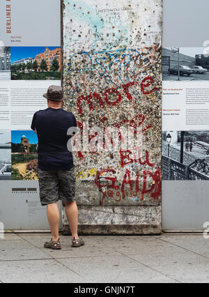 A tourist views at a section of the Berlin Wall on display at Potsdamer Platz Berlin Germany - Stock Photo