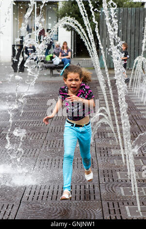Child playing in the water feature fountains and water jets in Williamson Square, Liverpool, Merseyside, UK - Stock Photo