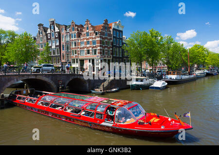 Tourist boat takes tour cruise group sightseeing on Dutch canals, Prinsengracht and Brouwersgracht, Amsterdam, Holland - Stock Photo