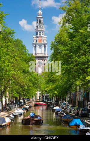 View of Zuiderkerk in Old Town and tourist boat taking tour group along Dutch canals, Groenburgwal in Amsterdam, - Stock Photo