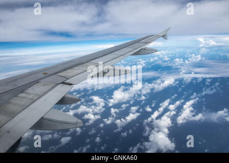 A view of a passenger jet wing as seen from the cabin during flight - Stock Photo