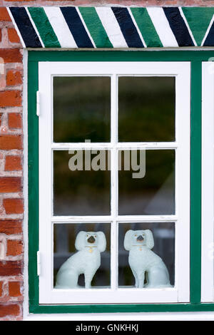 Traditional Staffordshire dog figurines in window of cottage house on Fano Island, South Jutland, Denmark - Stock Photo