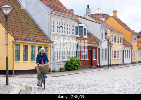 Woman cycling in Ramsherred cobbled street in old town in Odense on Funen Island, Denmark - Stock Photo
