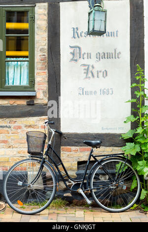 Traditional bicycle at restaurant Den Gamle Kro 17th Century in Nedergade in Odense on Funen Island, Denmark - Stock Photo
