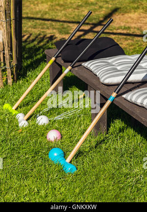 Image of croquet bats and balls in the garden. - Stock Photo