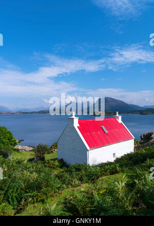 Small white cottage with red roof beside Loch Shieldaig in Torridon, on North Coast 500 tourist route, Highland, - Stock Photo