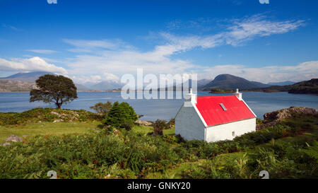 Small cottage with red roof beside Loch Shieldaig in Torridon, on North Coast 500 tourist route, Highland, Scotland, - Stock Photo