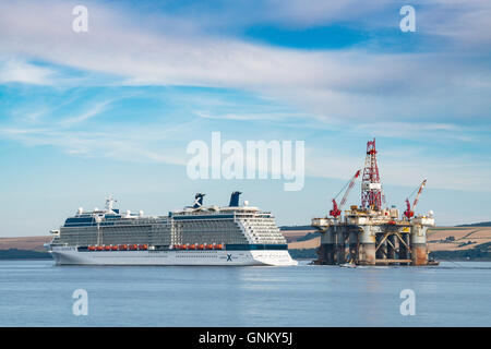 Luxury cruise liner Celebrity Silhouette passing oil rig, leaving port of Invergordon in Ross and Cromarty,Highland, - Stock Photo