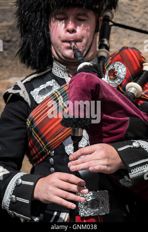 Detail of man playing bagpipes for tourists wearing traditional military uniform with tartan and kilt in Edinburgh, - Stock Photo