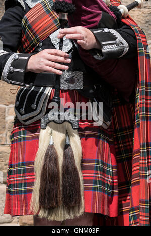 Detail of man playing bagpipes wearing traditional military uniform with tartan and kilt in Edinburgh, Scotland, - Stock Photo