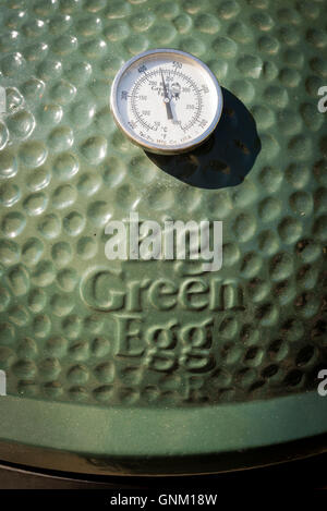 Close up of the temperature gauge and logo on a Big Green Egg Barbecue - Stock Photo