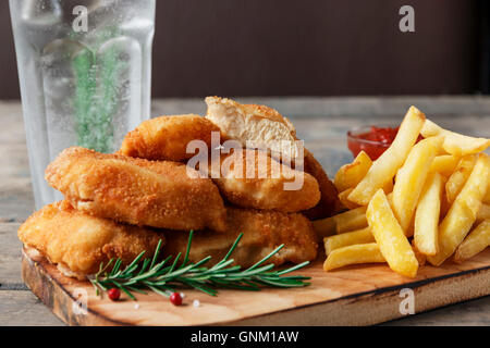 chicken nuggets french fries on the board with red sauce - Stock Photo