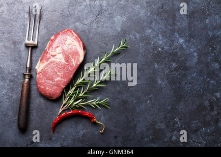 Raw beef steak cooking and ingredients. Meat piece, herbs and spices. Top view with copy space over stone table - Stock Photo