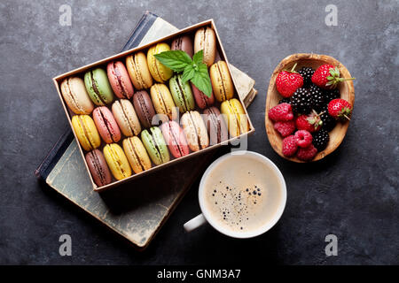 Colorful macaroons and berries on stone table. Sweet macarons and coffee cup. Top view - Stock Photo