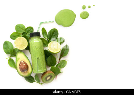Bottled green smoothie surrounded by green foods including spinach and kiwi - Stock Photo