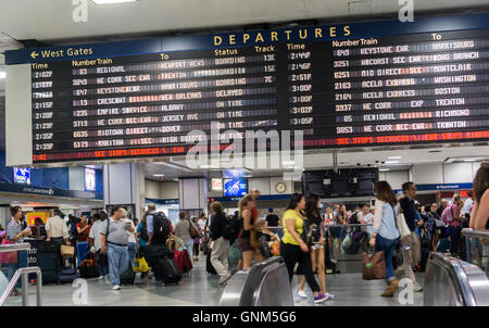 Travelers for Amtrak and NJ Transit in Penn Station in New York on Friday, August 26, 2016 wait by the schedule - Stock Photo
