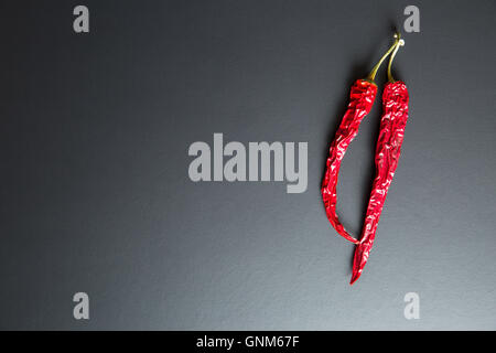 Two dried chili peppers on black background. - Stock Photo