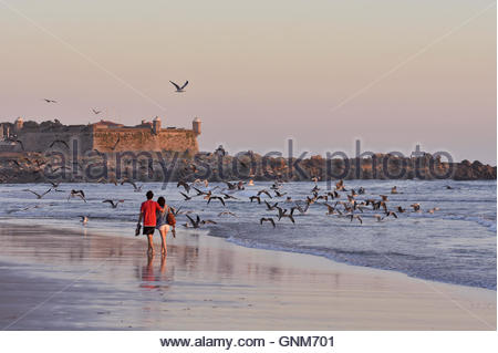 Couple walking on Matosinhos Beach at dusk near Porto Portugal Europe. Castelo do Queijo fortified castle in background. - Stock Photo