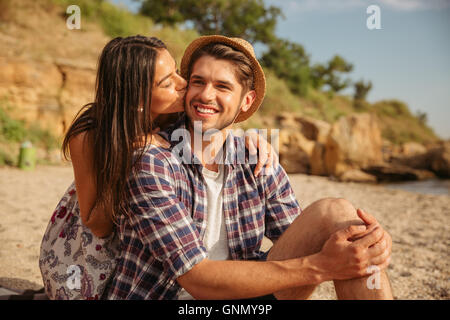 Happy young cheerful couple kissing while having fun camping at the beach - Stock Photo