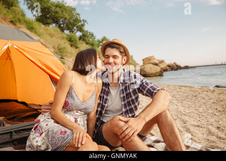 Young couple kissing while sitting at the camping tent outdoors - Stock Photo