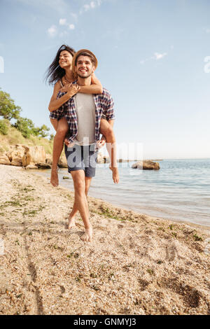 Handsome smiling young man giving piggy back ride to his girlfriend at the beach - Stock Photo