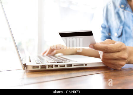 Woman sitting using her computer/laptop with credit card for shopping goods online. Online shopping concept. - Stock Photo