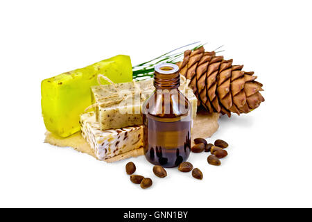 Cedar oil in a bottle, a bump, three homemade soap nuts isolated on white background - Stock Photo