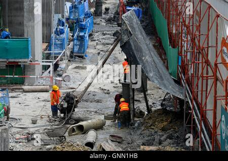 Construction workers at wet building site with scaffolding and tools including machine Bangkok Thailand - Stock Photo