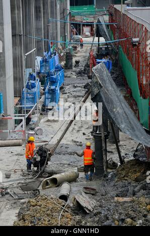 Construction workers at building site with blue scaffolding and tools including pump Bangkok Thailand - Stock Photo