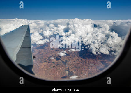 Aircraft wing seen through the window during fly over clouds - Stock Photo